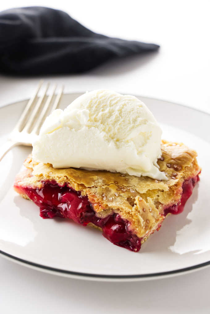 A serving of strawberry-rhubarb slab pie with a scoop of ice cream