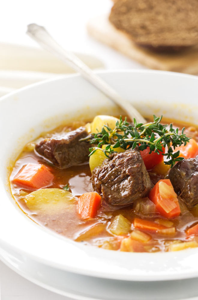 A bowl of soup with chunks of lamb and vegetables