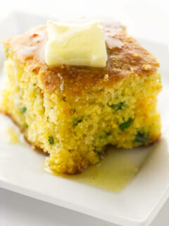 A slice of jalapeno cheddar cornbread with butter on top.