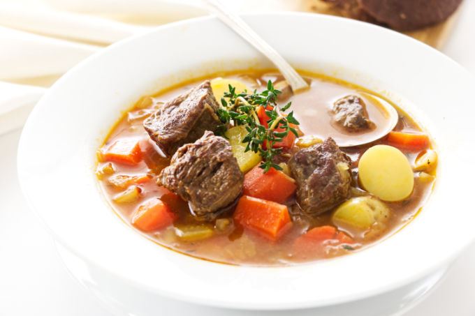 A bowl of lamb and vegetable soup with soup spoon