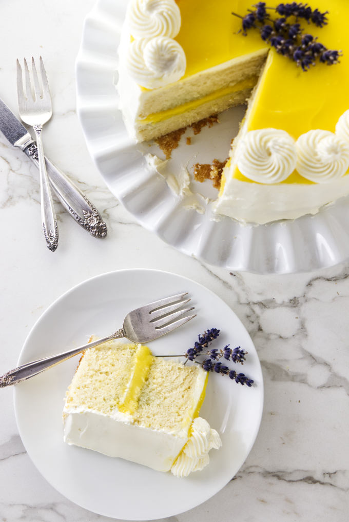 A lemon lavender cake on a cake plate with a slice of cake on a dessert plate.