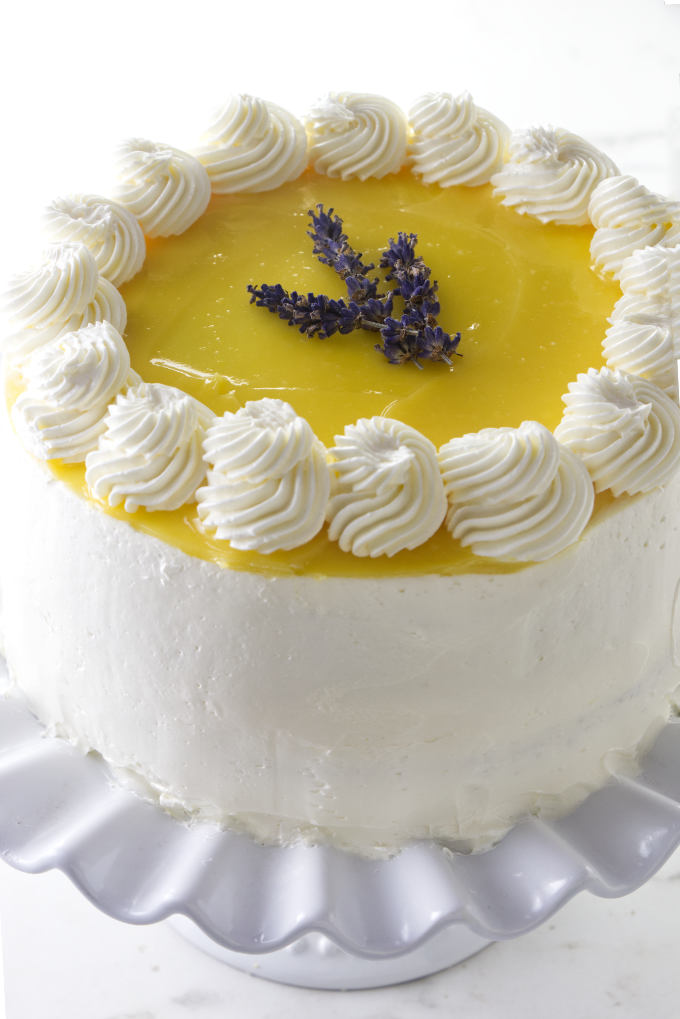 A lemon lavender cake on a cake plate with lavender buds on top.
