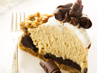 A slice of peanut butter pie with chocolate curls and graham cracker crust.