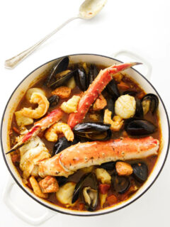 A pot of seafood stew with king crab, shrimp, scallops, mussels, halibut, and salmon.