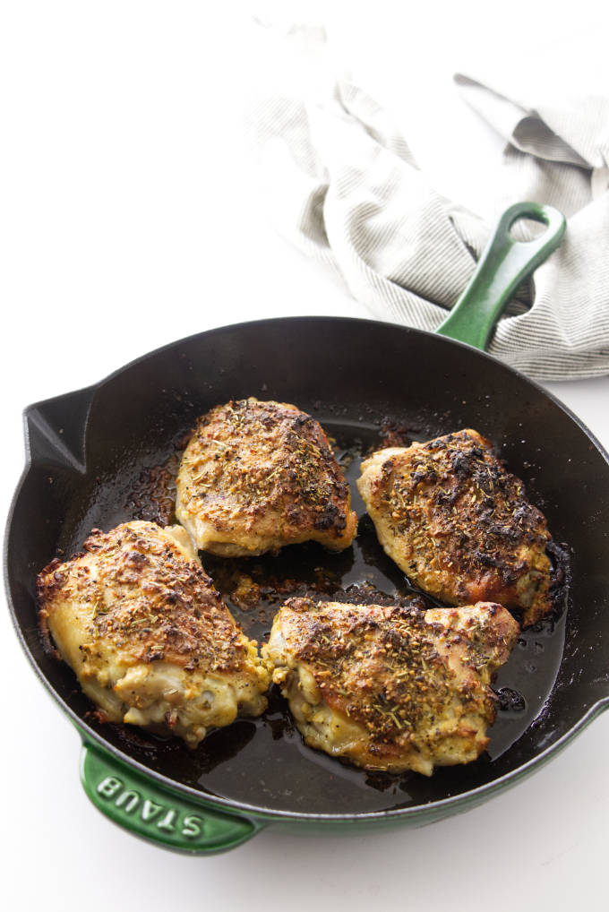 Four roasted chicken thighs in a skillet