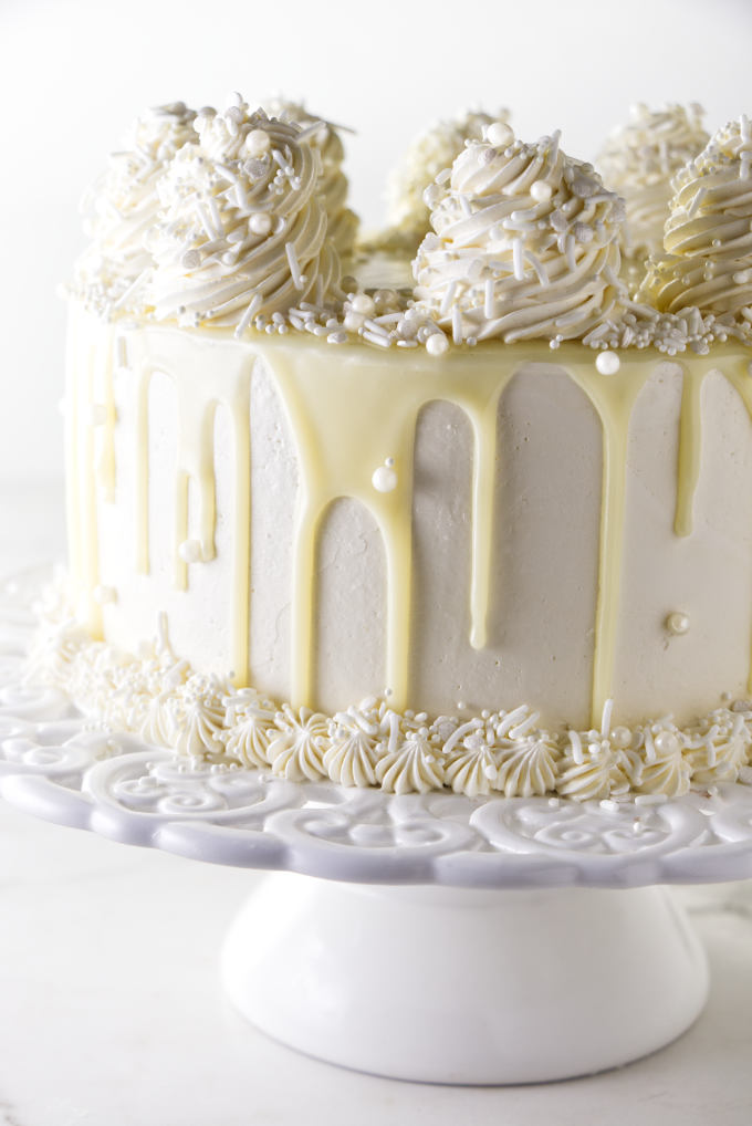 A white chocolate cake with white chocolate ganache dripping down the sides.