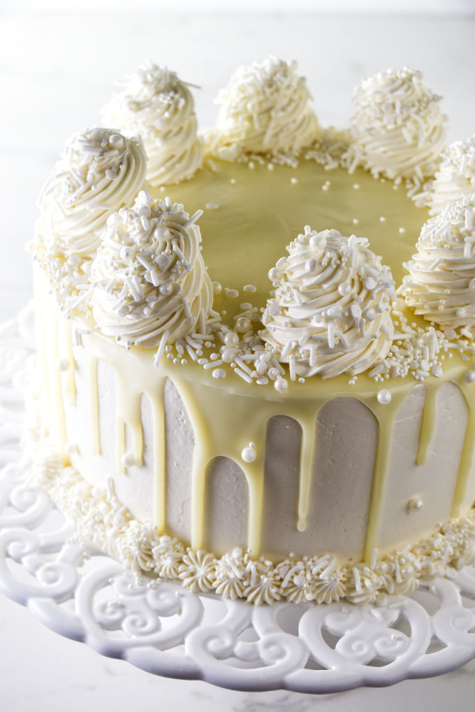 A white chocolate cake on a cake platter.