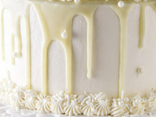 White chocolate ganache dripping down the sides of a cake.