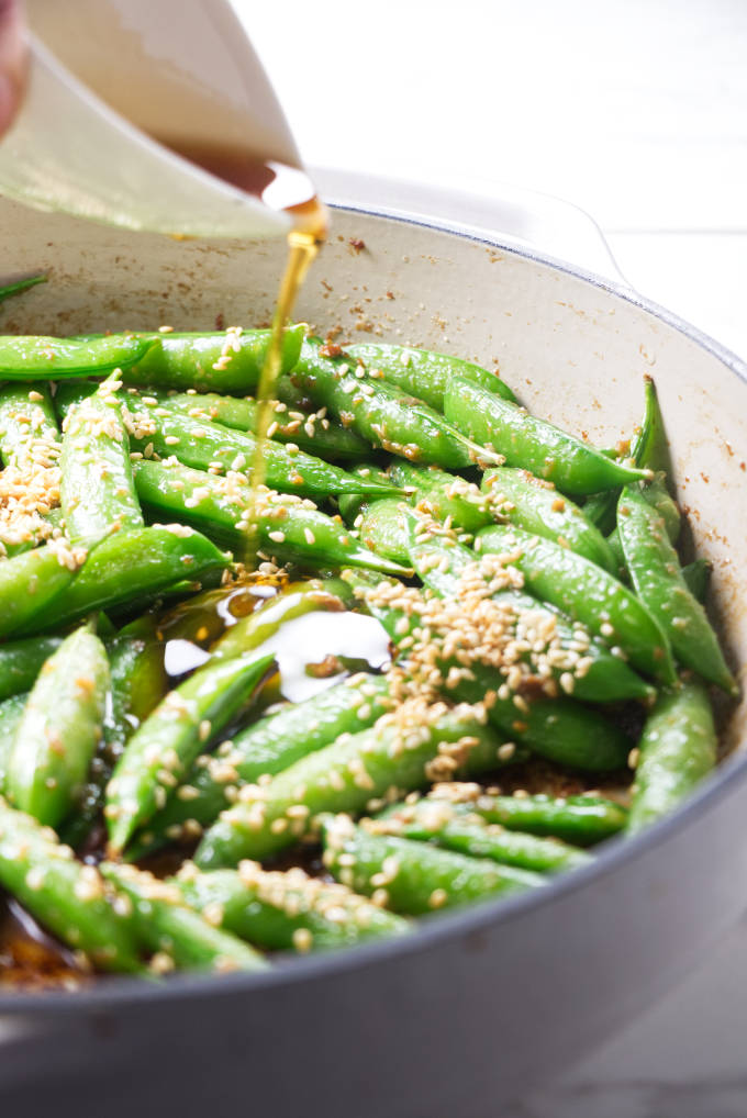 Pouring toasted sesame oil on sugar snap peas.