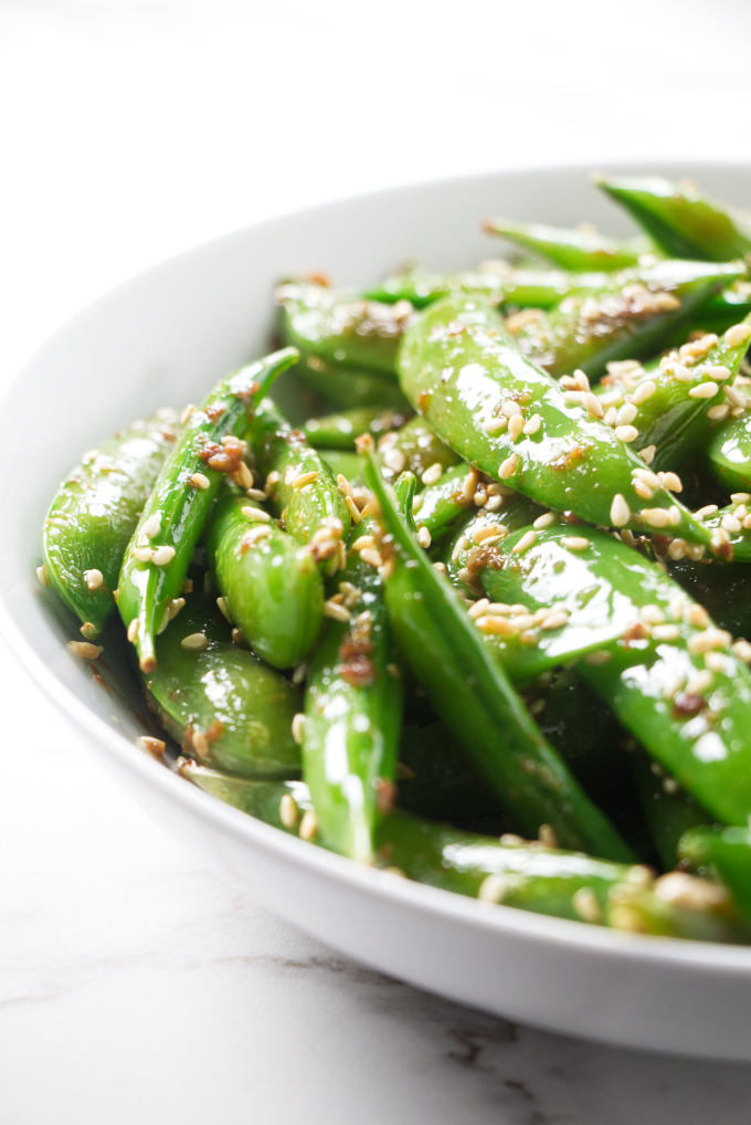 A bowl of sugar snap peas with garlic and sesame.