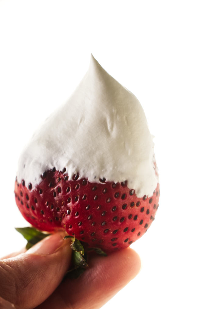 Whipped cream covering a strawberry.