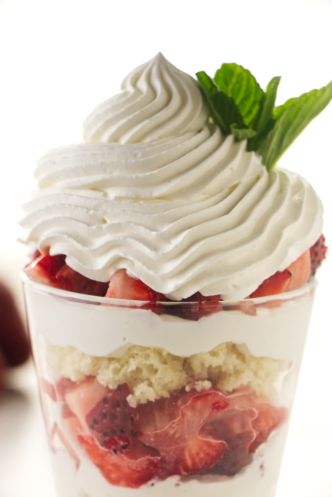 Whipped cream pipped on top of a strawberry parfait.