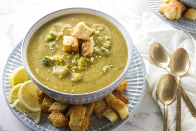 A bowl of chunky lemon broccoli soup next to three spoons.