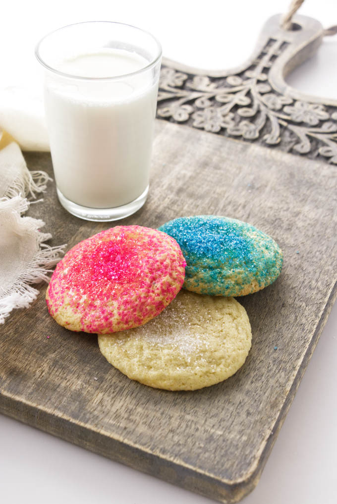 Three sugar cookies on a tray with milk.