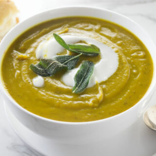 A bowl of sweet potato soup with fried sage on top.