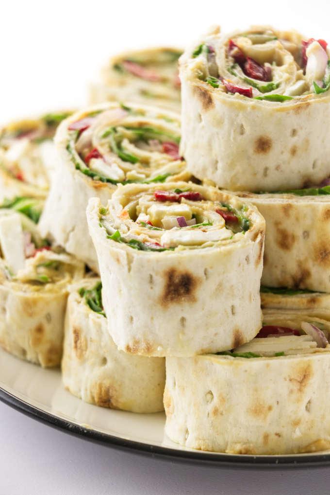A stack of vegetarian hummus pinwheels.