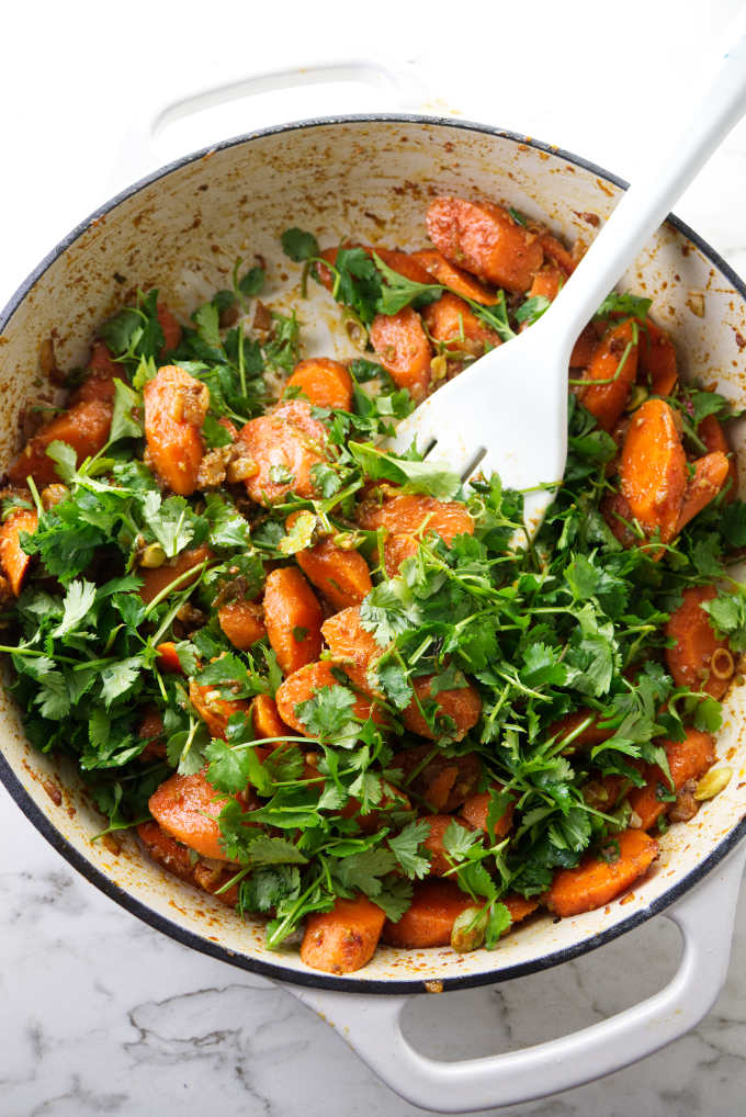 Sliced carrots in a skillet being tossed with cilantro.