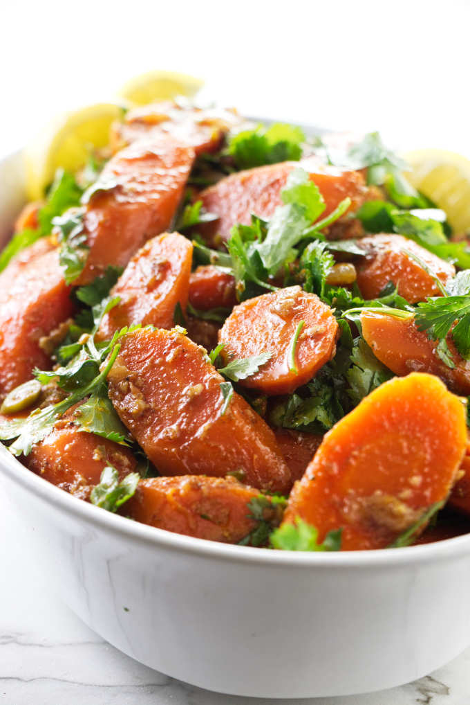 Moroccan carrot salad in a dish with lemon wedges.