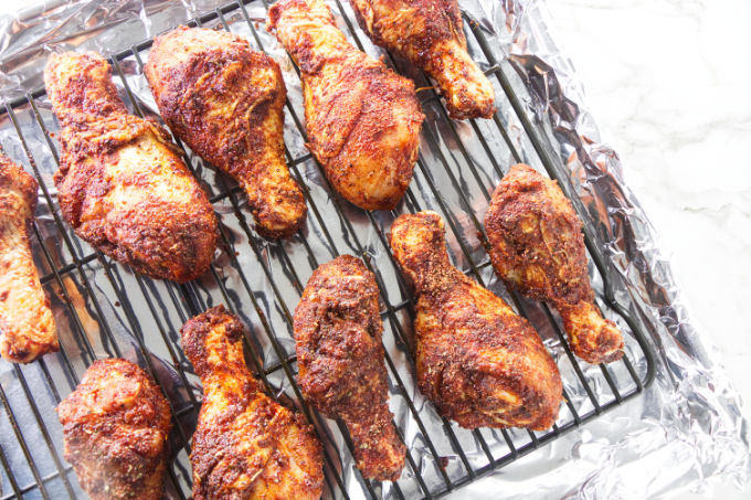Chicken legs in a sheet pan getting ready for the oven.