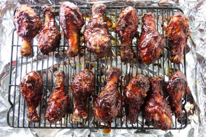 Baked chicken legs on a rack over a sheet pan.