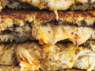 Four kimchi grilled cheese sandwiches stacked on top of each other.