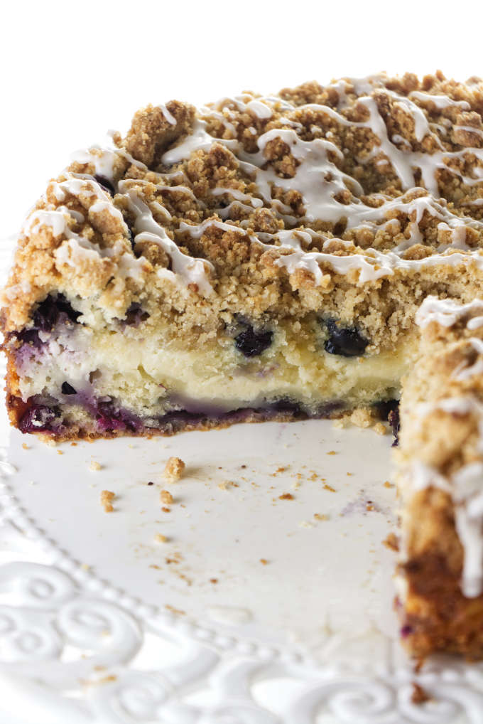 A blueberry coffee cake with a cheesecake center sliced and sitting on a cake plate.