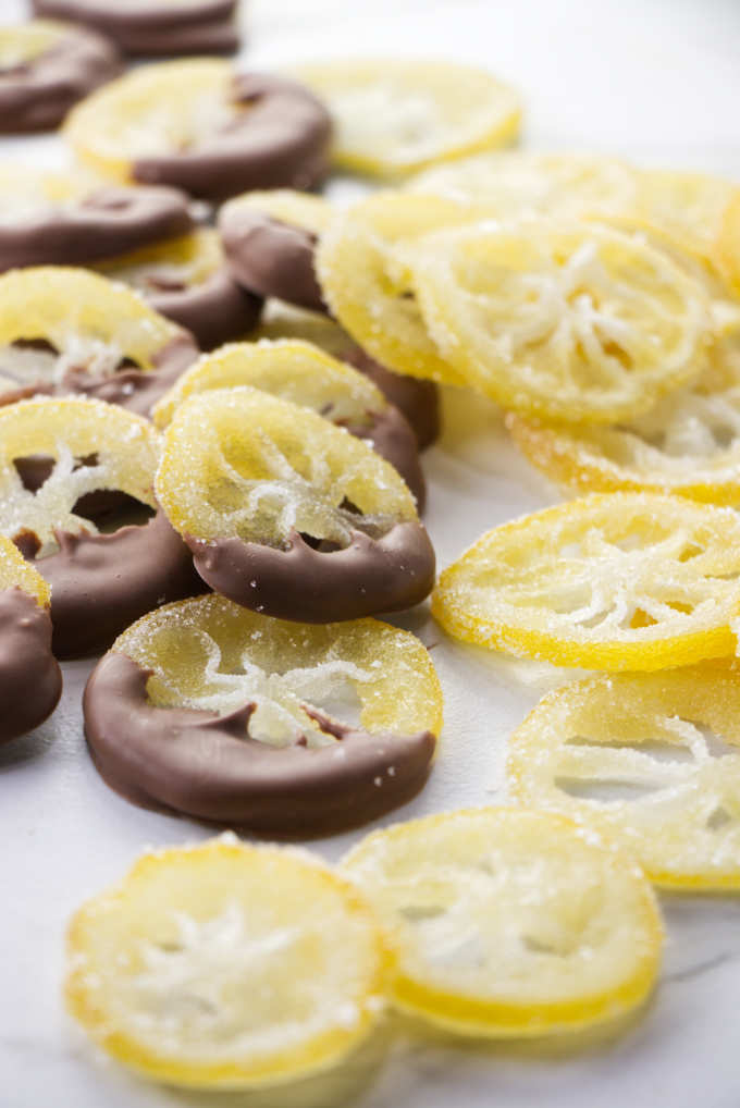 A pile of candied lemon slices coated in sugar with some of them dipped in chocolate.