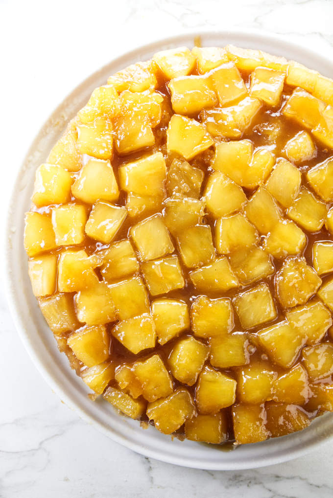 An overhead view of a pineapple upside down cake with pineapple chunks on top.