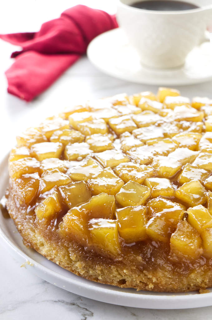 A pineapple upside down cake with a cup of coffee in the background.
