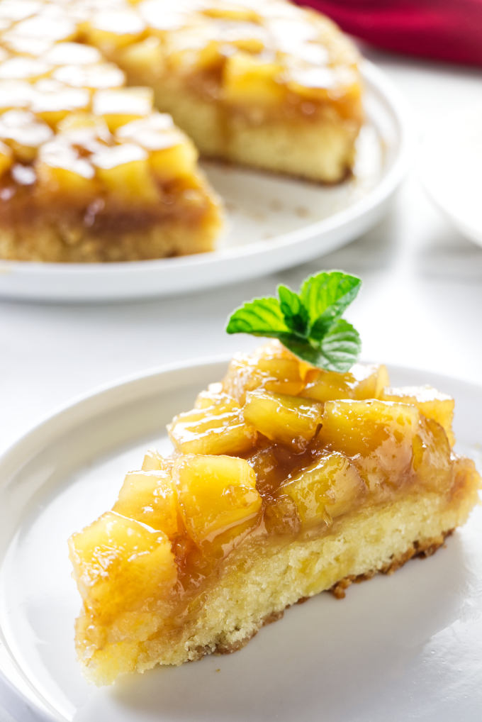 A slice of pineapple upside down cake with pineapple chunks.
