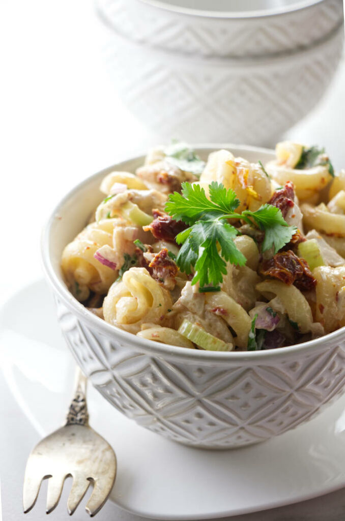 A dish of pasta salad with chicken and chipotle dressing.
