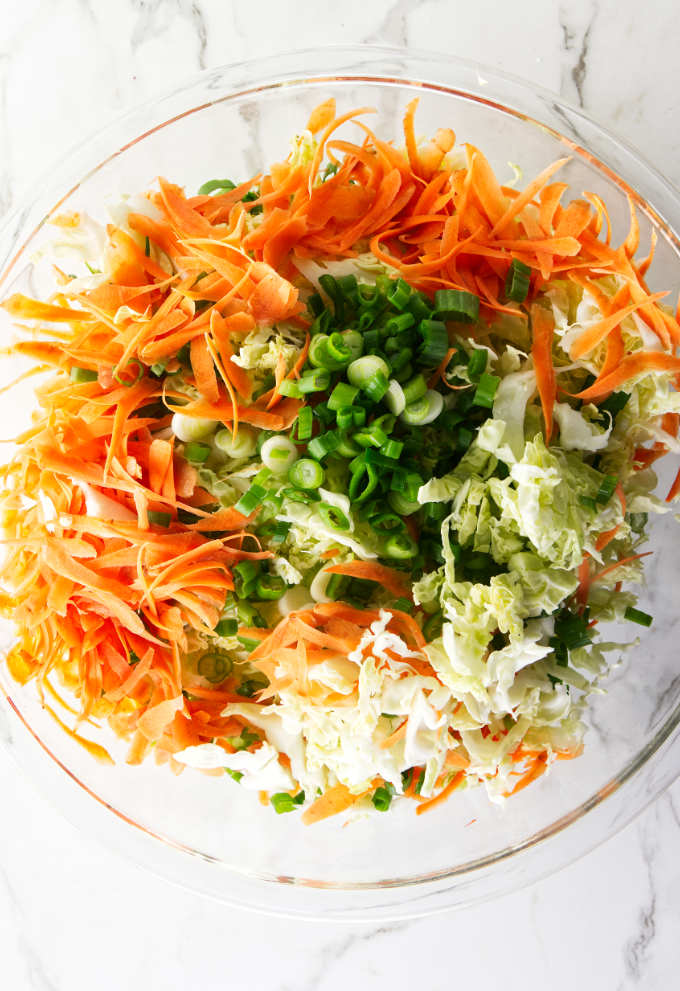 Shredded carrots, shredded cabbage and chopped green onions in a bowl.