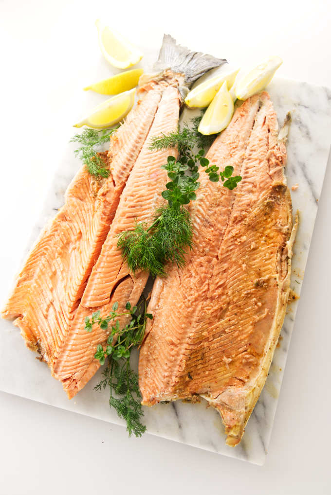 A whole baked salmon opened up on a serving platter.