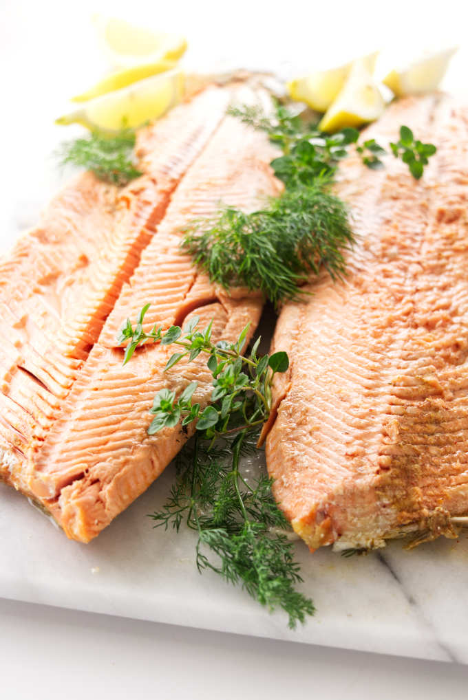 A whole baked salmon with fresh herbs.