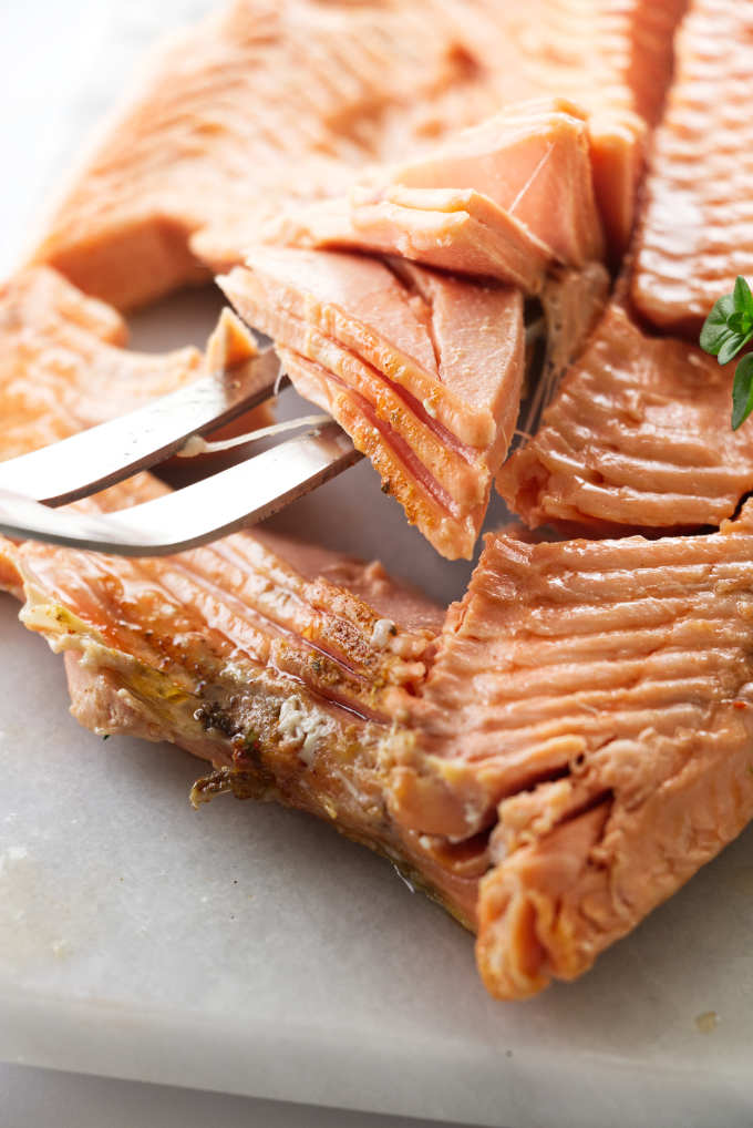 A fork lifting up on the flesh of a freshly baked whole salmon.