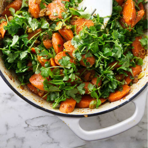 Tossing carrot salad with cilantro leaves.