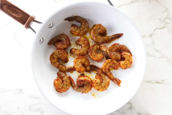 Cooking blackened shrimp in a saute pan.