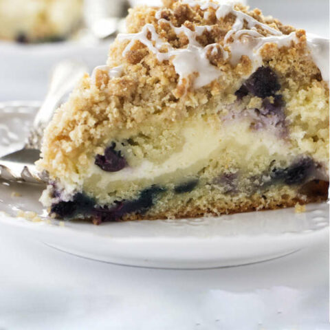 A slice of blueberry coffee cake filled with cheesecake.