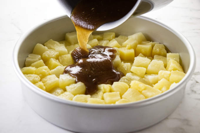 Pouring brown sugar mixture over pineapple chunks in a cake pan.