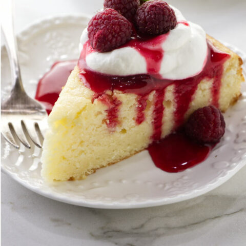A slice of lemon ricotta cake with raspberry sauce dripping down the sides.