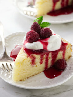 A slice of lemon ricotta cake with raspberry sauce and whipped cream on top.