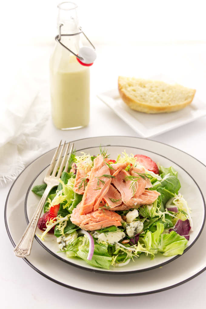 A Serving of salmon salad on a plate, preserved lemon vinaigrette and bread in the backbround
