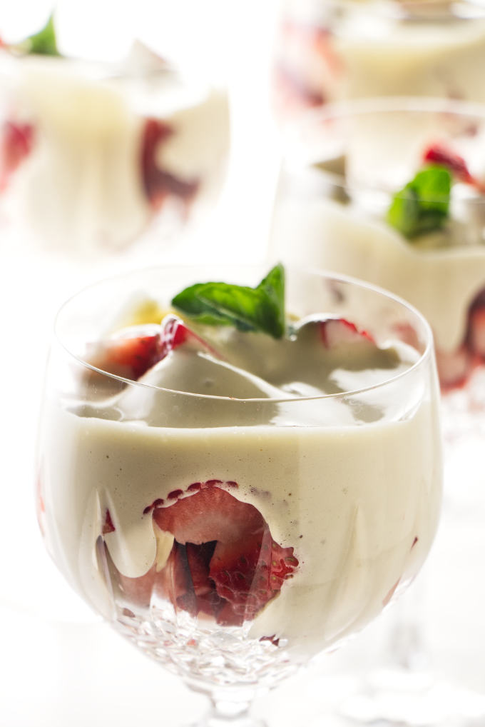 Four wine glasses filled with zabaglione and strawberries.