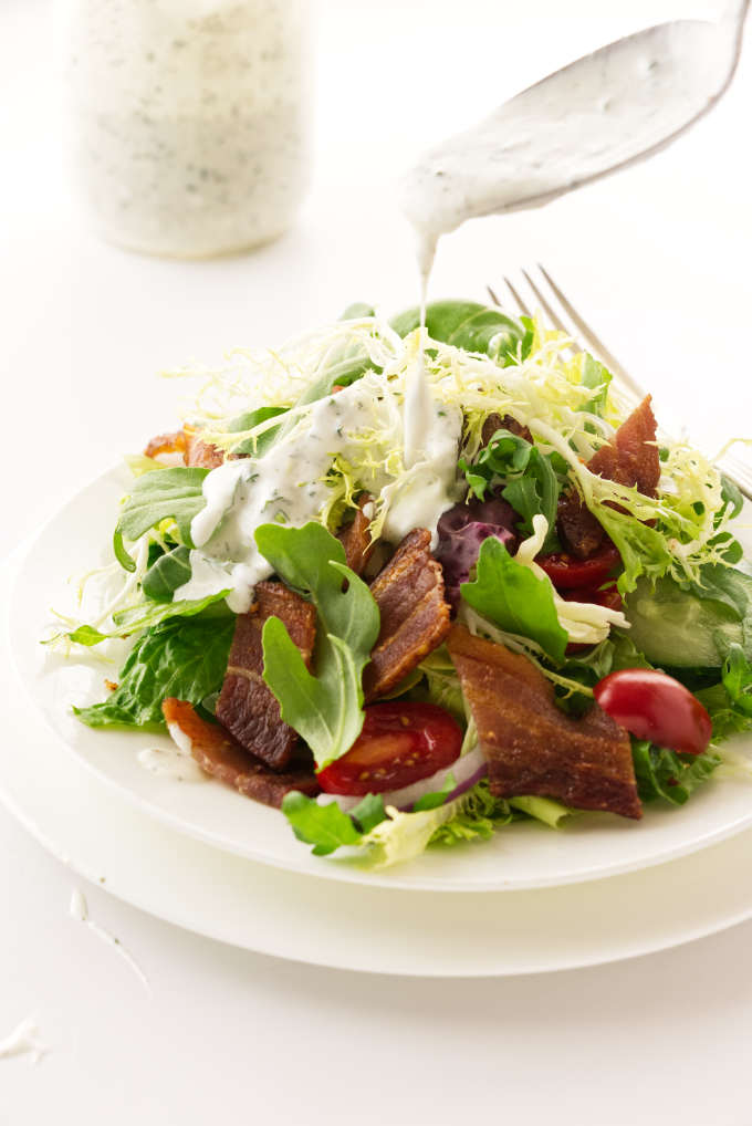 Green salad with dressing being spooned on