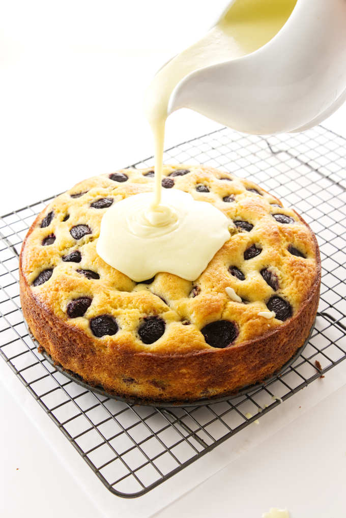 Cherry cake with white chocolate ganache being poured on top