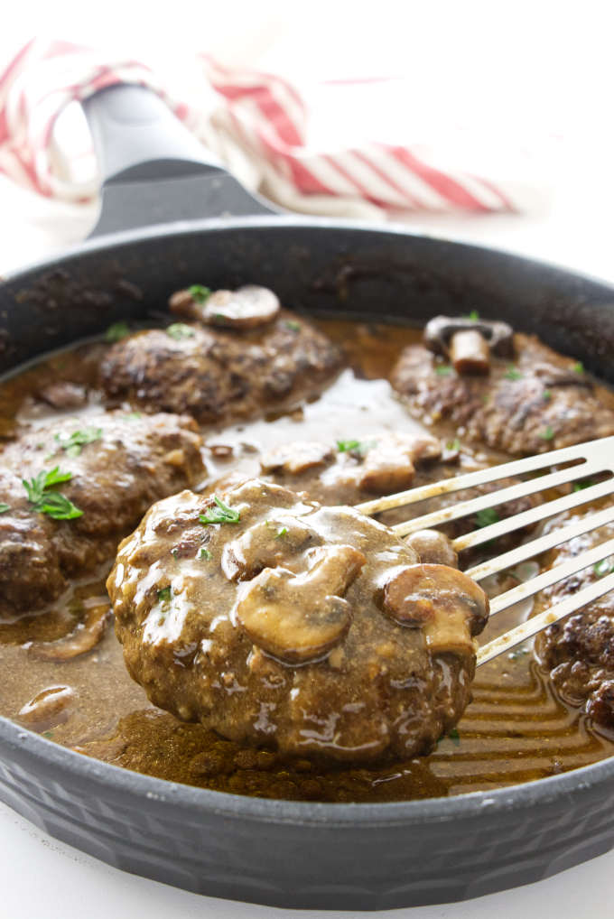 Salsbury steak being lifted from skillet