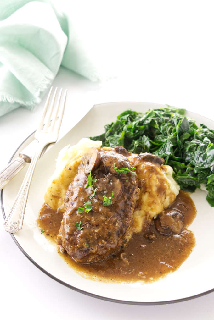 Serving of salisbury steak on mashed potatoes with a side of sauteed greens