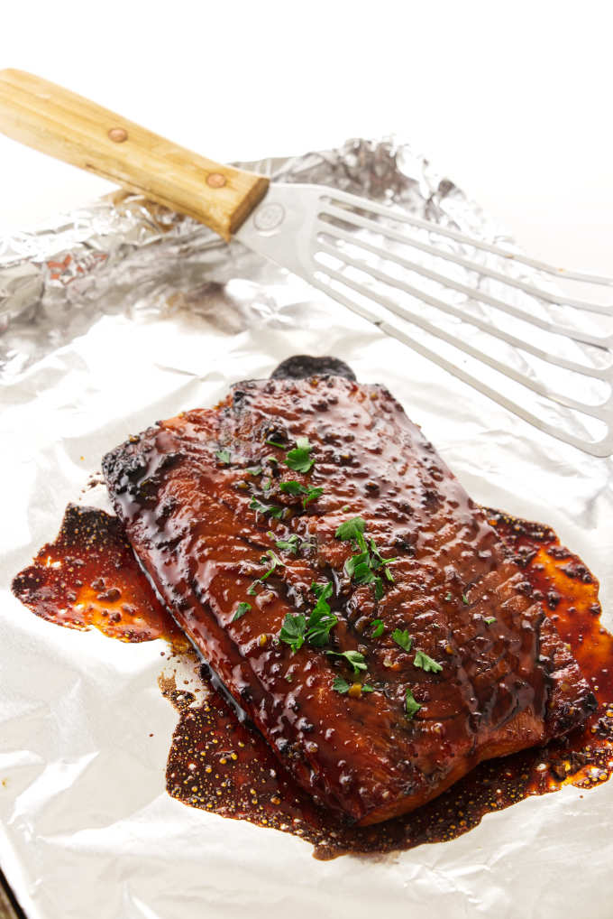 A fillet of salmon on a baking sheet with honey bourbon glaze.
