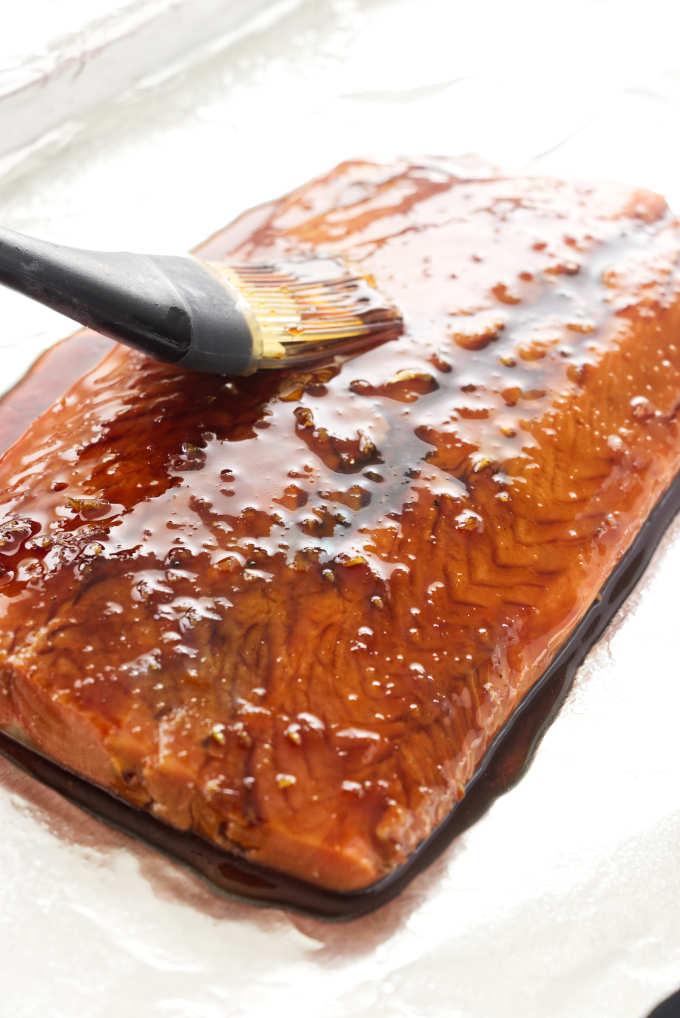 Coating honey bourbon glaze on a salmon fillet.