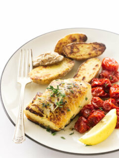 Overhead view of a butterr-thyme basted sea bass filet, roasted fingerling potatoes and grape tomatoes